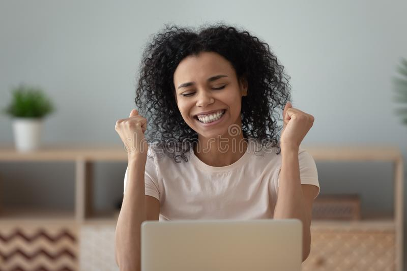 Overjoyed happy african girl student celebrate great exam results. Overjoyed happy african black girl student winner read good internet news celebrate success royalty free stock photography