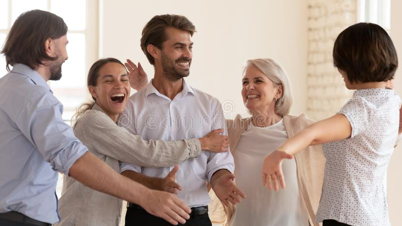 Overjoyed happy business people embrace male boss celebrate corporate success. Overjoyed funny business people scream embrace male boss celebrate corporate royalty free stock image