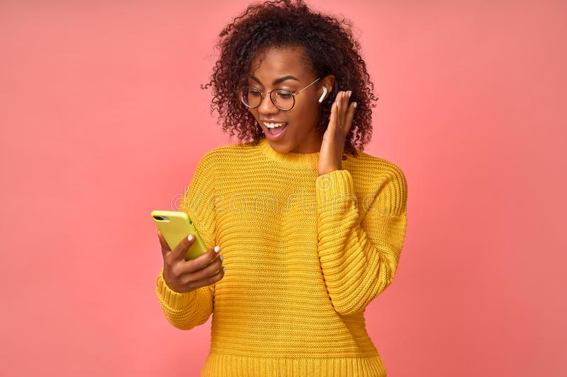 Overjoyed happy excited Afro American female glad to answers the video call using wireless earphones, rejoices good news stock photography