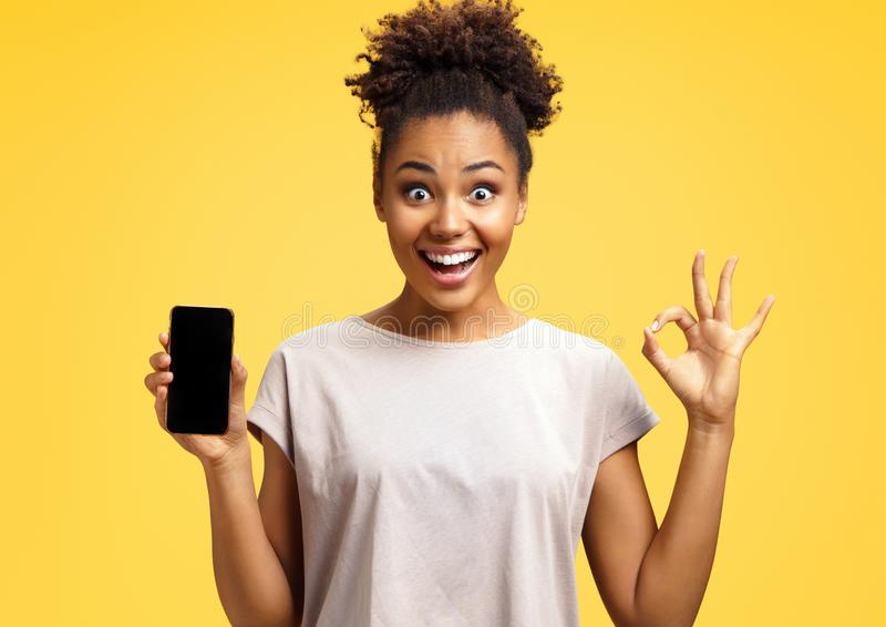 Overjoyed happy girl holds mobile phone and makes okay gesture. stock image