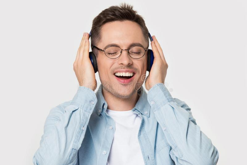 Overjoyed happy guy in eyeglasses enjoying favorite music. royalty free stock photos