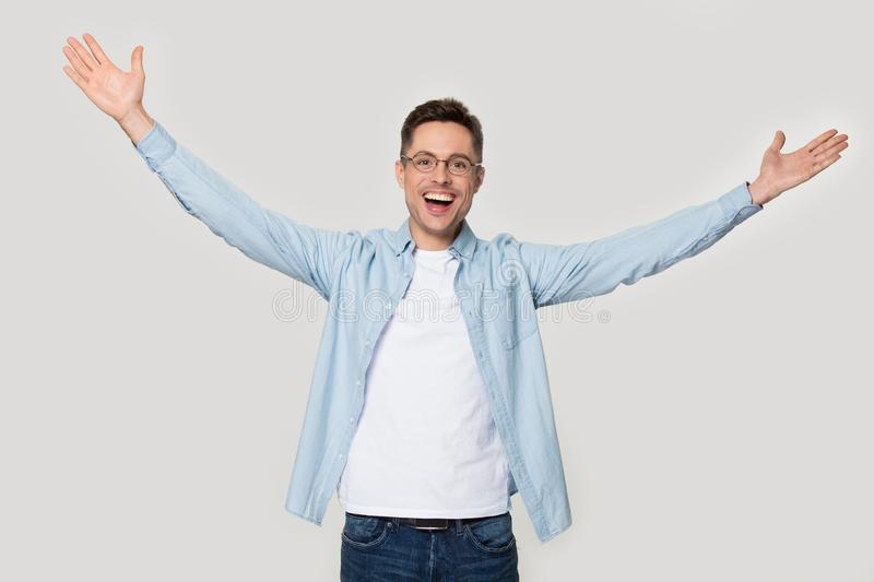 Overjoyed happy man standing with his hands wide open stock photo