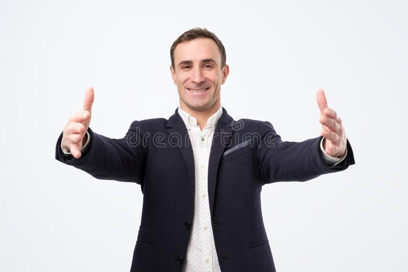 Overjoyed happy man in suit standing with his hands wide open welcoming his parners or friends royalty free stock image