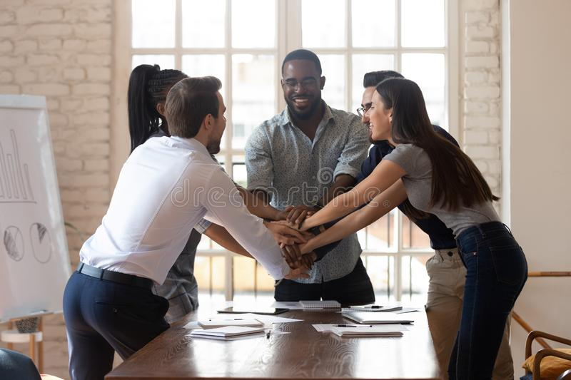 Overjoyed happy multiethnic young teammates celebrating employees unity at office. stock photo