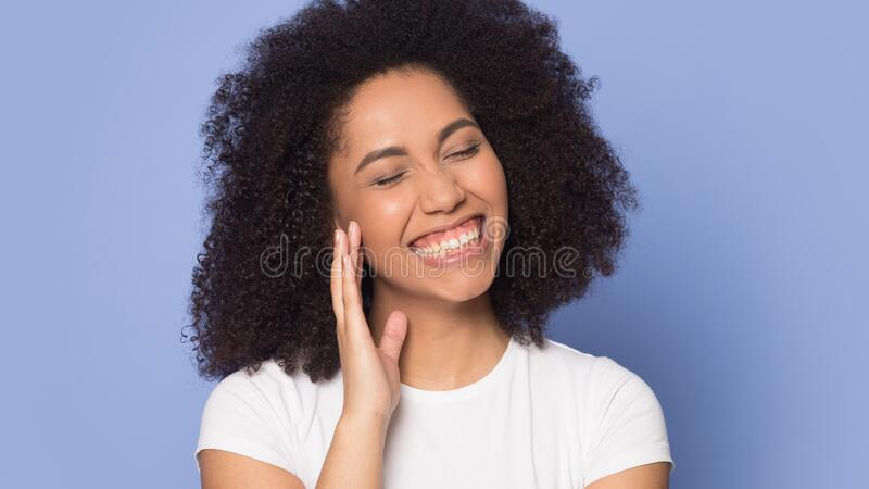Happy smiling african american young lady holding hand near ear. royalty free stock image