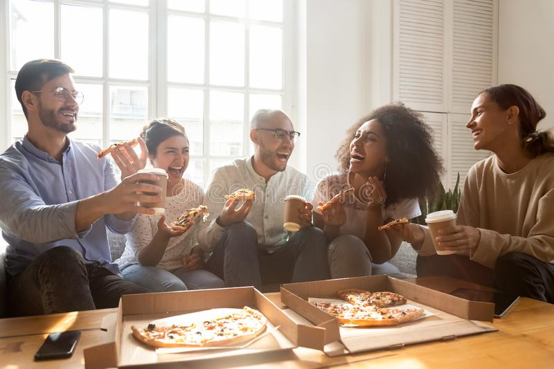 Excited multiracial young people have fun enjoying pizza royalty free stock photos