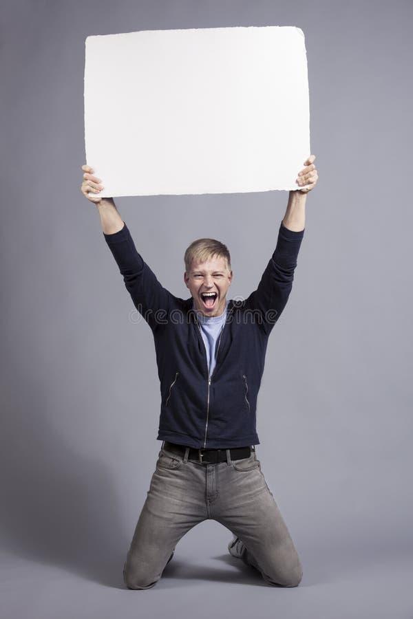 Overjoyed maninnehav upp tom signboard för vit. royaltyfri bild