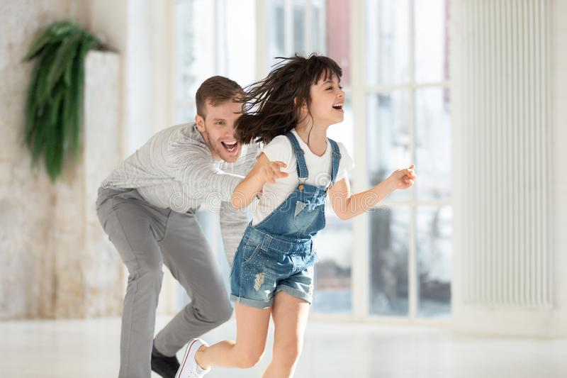 Overjoyed millennial man catching funny laughing running little daughter. royalty free stock photography