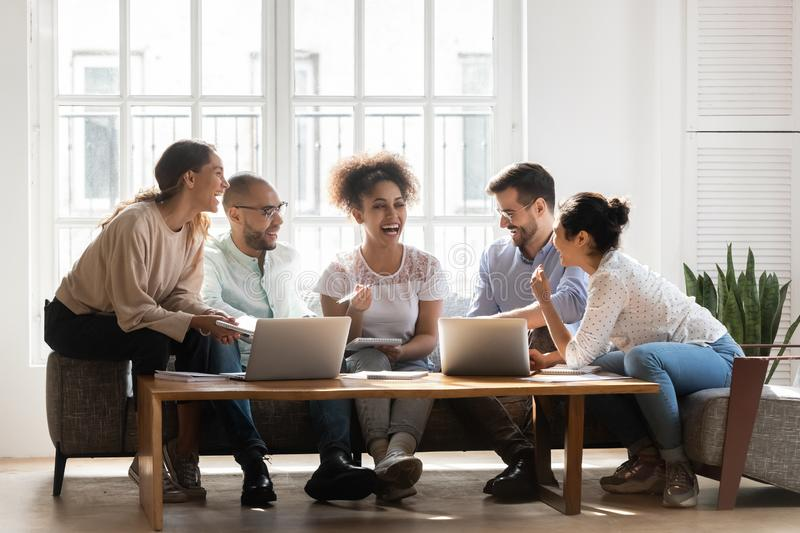 Overjoyed multiethnic young people have fun studying together stock images