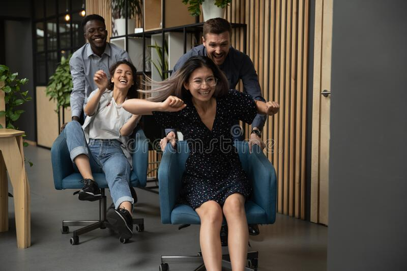 Overjoyed multiethnic colleagues have fun racing in office royalty free stock photos