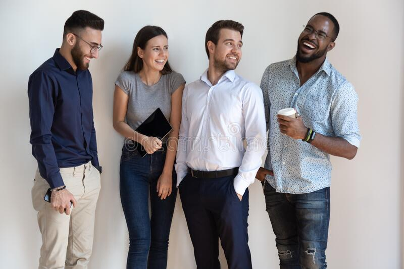 Overjoyed multiethnic millennial employees laugh posing together stock image