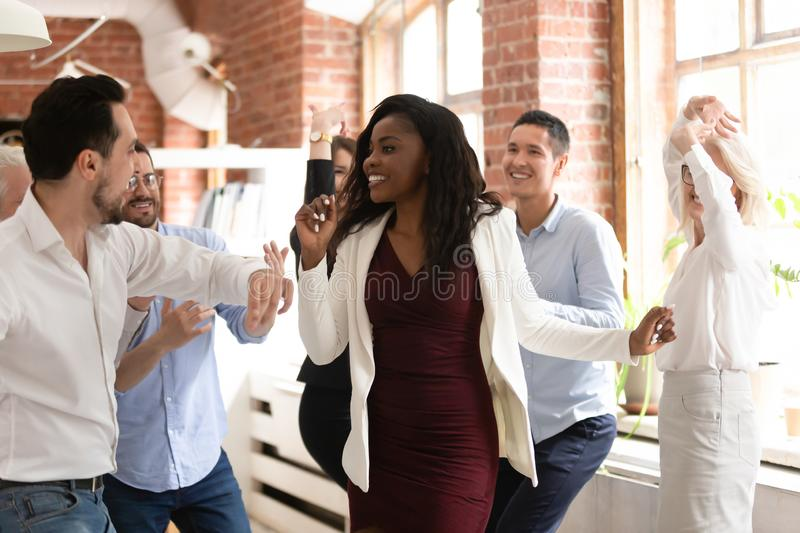 Happy diverse colleagues dance having fun in office. Overjoyed multiracial employees have fun celebrating shared business win or goal achievement, excited happy stock photos