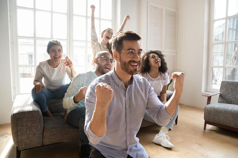 Overjoyed multiracial friends watch football at home online royalty free stock photo