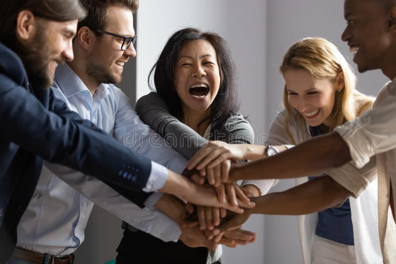 Overjoyed older asian businesswoman joining hands with young multiracial coworkers. Overjoyed older asian businesswoman joining hands with young multiracial royalty free stock image