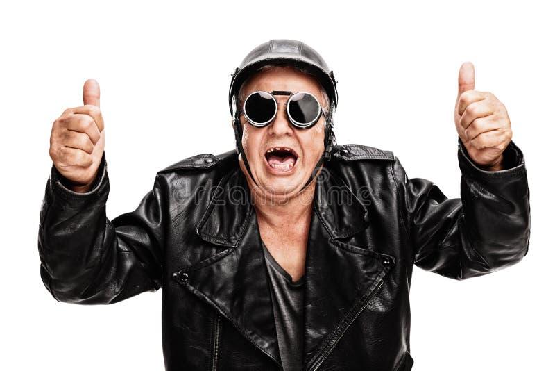 Overjoyed senior biker giving two thumbs up stock photo