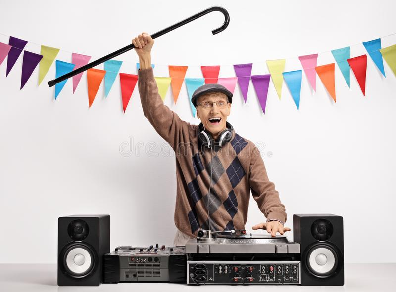 Overjoyed senior with a cane playing music on a turntable stock photography