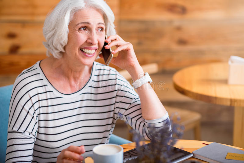 Overjoyed senior woman talking on cell phone. Full of gladness. Overjoyed smiling senior woman sitting at the table and talking on cell phone while resting stock photo