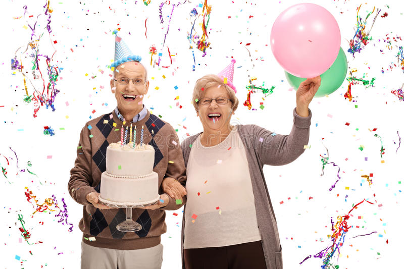 Overjoyed seniors celebrating a birthday with a cake and balloon. S isolated on white background royalty free stock photography