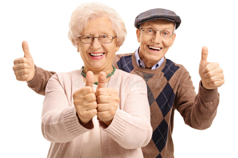 Overjoyed seniors holding their thumbs up stock photography