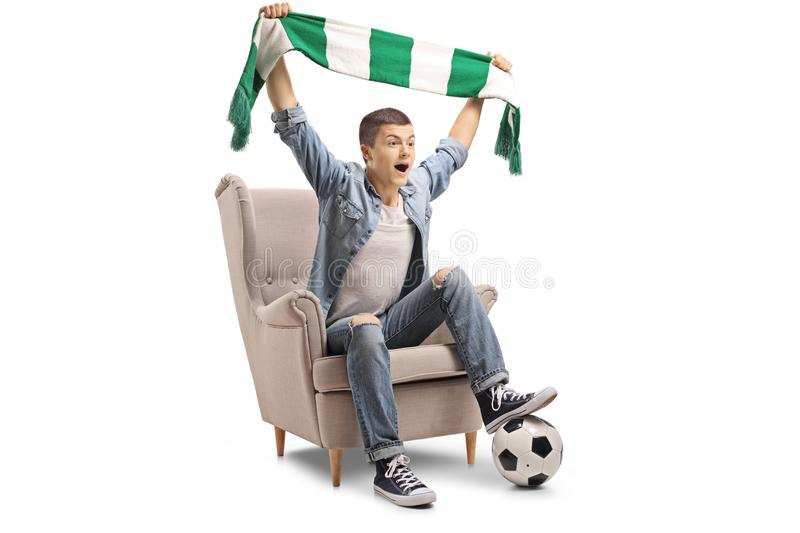 Overjoyed teenage soccer fan with a scarf and a football sitting royalty free stock images