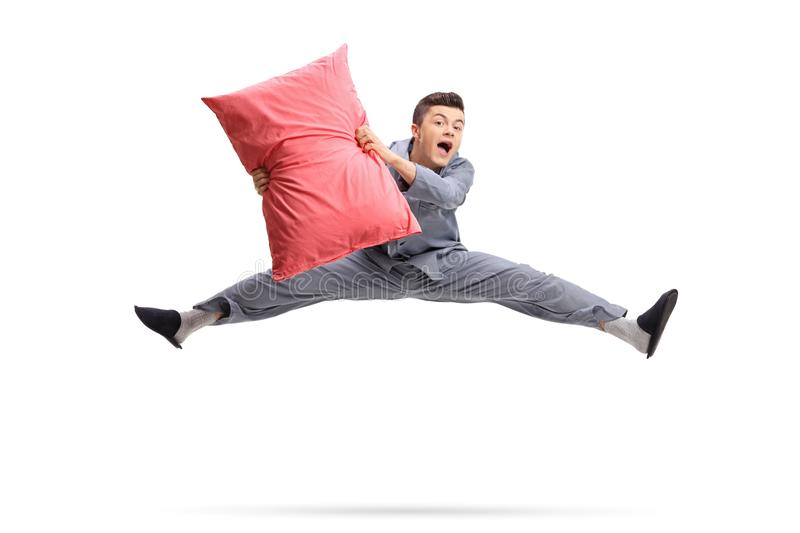 Overjoyed teenager in pajamas holding a pillow and jumping. Isolated on white background stock photo