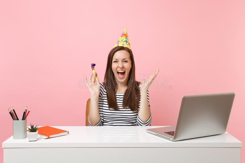 Overjoyed woman in birthday party hat with playing pipe screaming celebrating while sit work at desk with pc laptop. Isolated on pastel pink background royalty free stock photo
