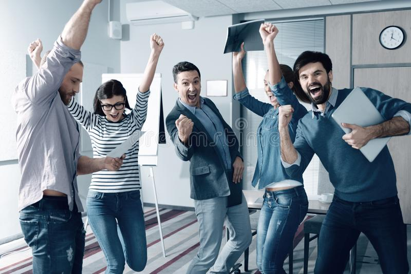 Overjoyed young colleagues celebrating a successful project royalty free stock images