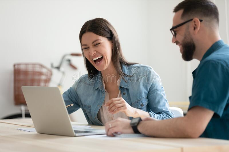Overjoyed young colleagues looking at computer screen. stock photography