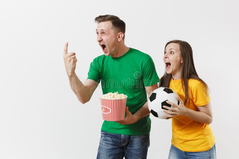 Overjoyed young couple, woman man, football fans in yellow green t-shirt cheer up support team with soccer ball bucket stock images