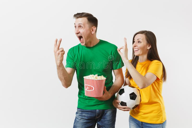 Overjoyed young couple, woman man, football fans in yellow green t-shirt cheer up support team with soccer ball bucket stock photography