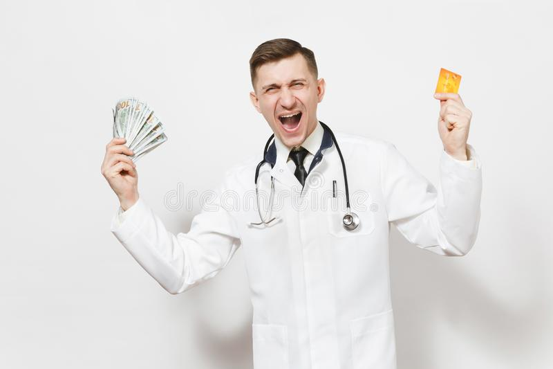 Overjoyed young doctor man isolated on white background. Male doctor in medical uniform stethoscope holding bundle of. Dollars, banknotes cash money, credit stock photo