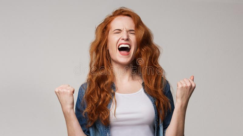 Overjoyed young redhead woman screaming with joy royalty free stock images
