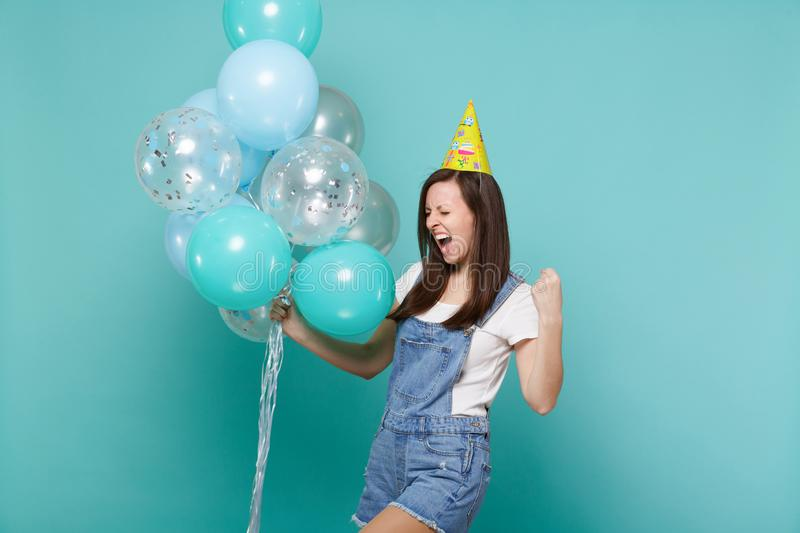 Overjoyed young woman in birthday hat screaming doing winner gesture, celebrating, holding colorful air balloons. Isolated on blue turquoise background royalty free stock image