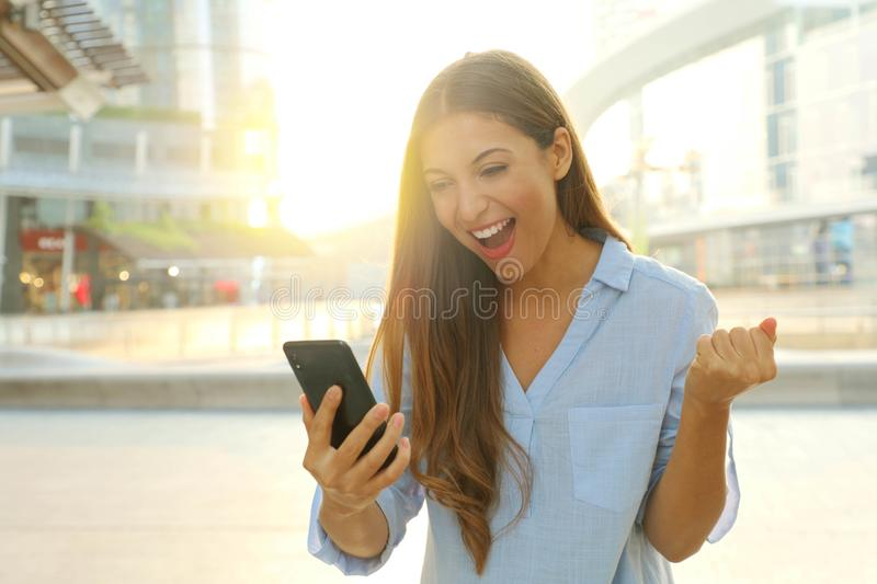 Overjoyed young woman reading message from friend on mobile expressing happiness about great news. Emotional female excited with royalty free stock image