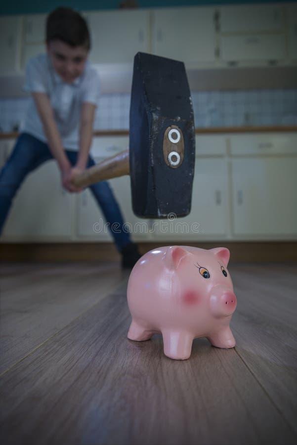 Overkill on piggy bank. Little boy swinging a big hammer towards a piggy bank. shallow depth of fiield royalty free stock image