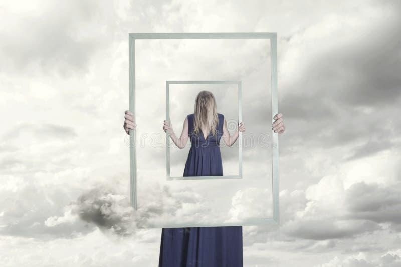 Overklig bild av en kvinna som rymmer en ram som reflekterar sig royaltyfri foto