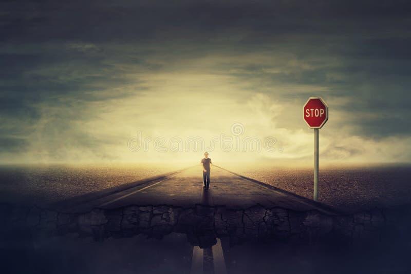 Overklig sikt, som mannen går en krossande asfaltväg, som det röda tecknet för STOPPET varnar av fara Djupt hål i jordningen, sva royaltyfri fotografi