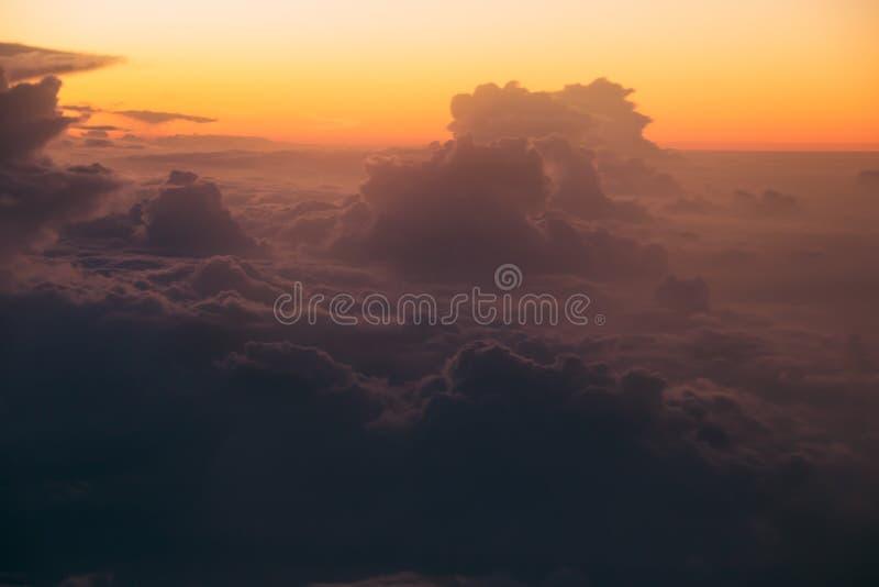 Overklig soluppgång över mörker fördunklar till och med fönsterflygplanet slapp fokus royaltyfria bilder