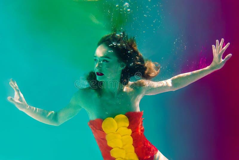 Overklig stående av den unga attraktiva kvinnan med luftbubblor som är undervattens- i färgrikt vatten med färgpulver fotografering för bildbyråer