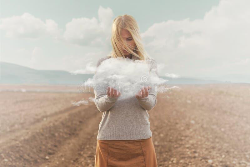 Overkligt ögonblick av en kvinna som rymmer ett moln i henne händer royaltyfri foto
