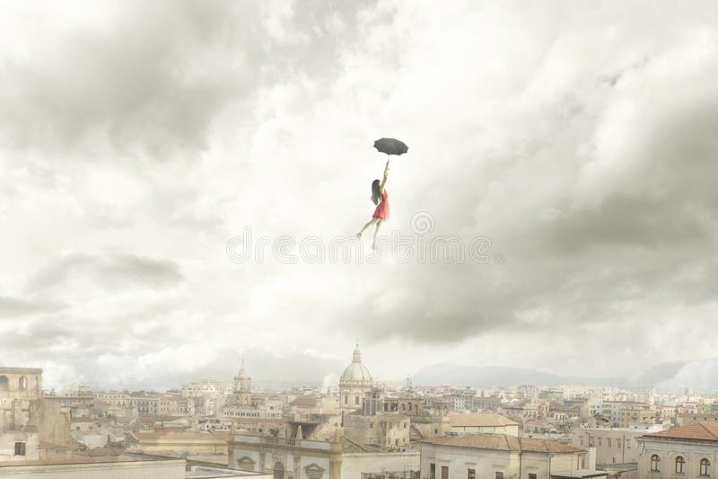 Overkligt ögonblick av ett kvinnaflyg med hennes paraply över staden royaltyfria bilder