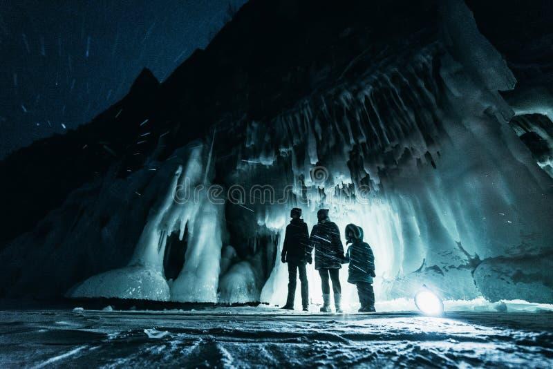 Overkligt landskap med folk som undersöker den mystiska isgrottagrottan utomhus- affärsföretag Familj som undersöker den enorma i arkivfoto