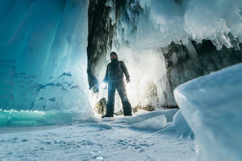 Overkligt landskap med mannen som undersöker den mystiska isgrottagrottan utomhus- affärsföretag Man som undersöker den enorma is arkivfoton