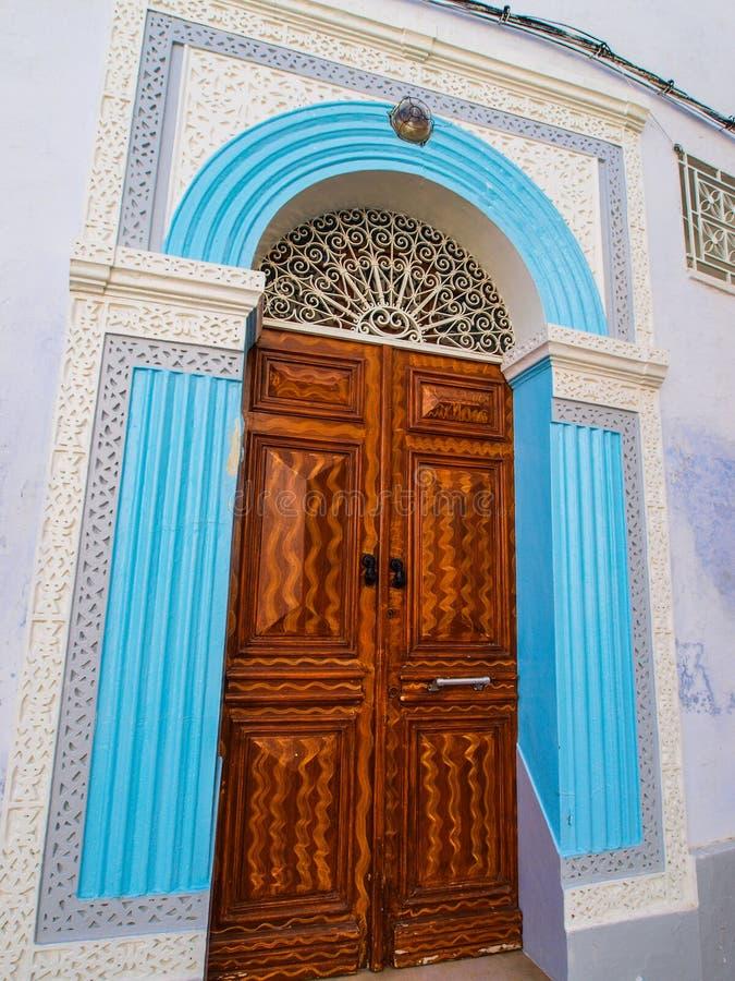 Overladen gesneden houten die deur door blauwe stinework in wordt omringd me stock foto's