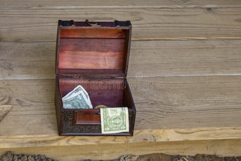 Overladen houten uiteindedoos met Amerikaanse dollars die op de rand van rustiek houten stadium zitten stock fotografie