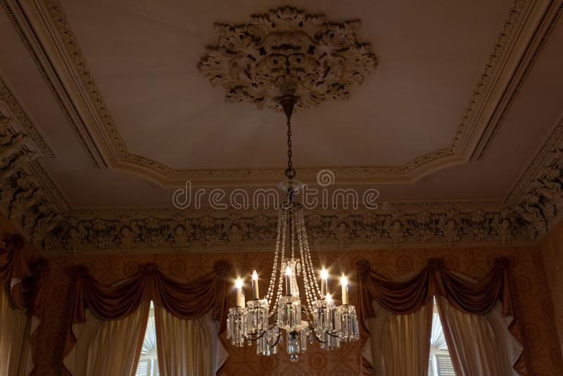 Overladen kristalkroonluchter in een mooie ruimte met extravagante gordijnen en pleisterafgietsels, zachte kleuren stock afbeeldingen