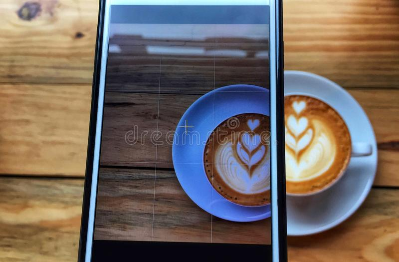 Overlay of image shooting in the phone and real blur hot cappuccino coffee in white cup and saucer on wooden table background. stock photos