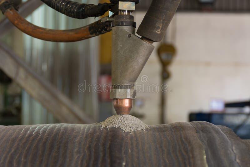 Overlay a superfície dura de solda do rolo de aço submergem perto o processo da soldadura de arco imagem de stock royalty free