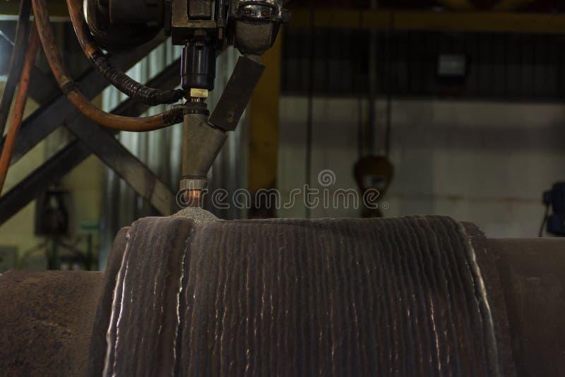 Overlay a superfície dura de solda do rolo de aço submergem perto o processo da soldadura de arco fotografia de stock