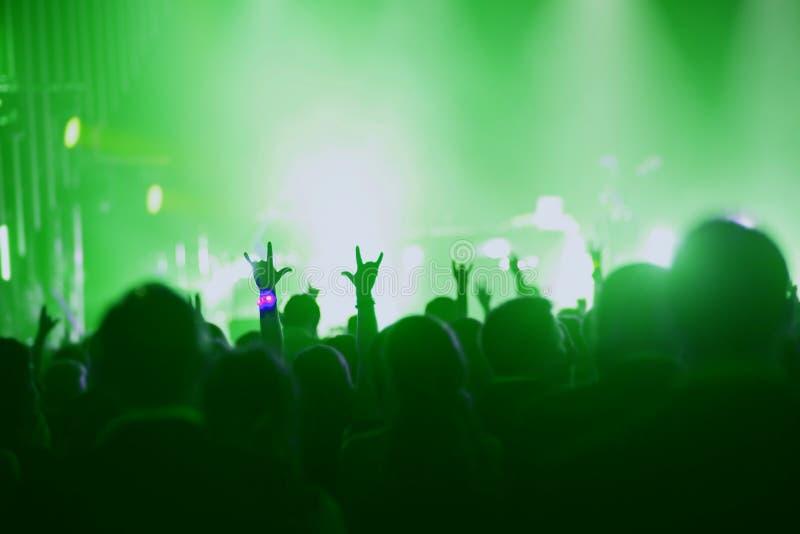 Overleg, gebeurtenis of partijconcept Mensen met handen omhoog bij scène, schijnwerper, gekleurd groen licht royalty-vrije stock afbeelding
